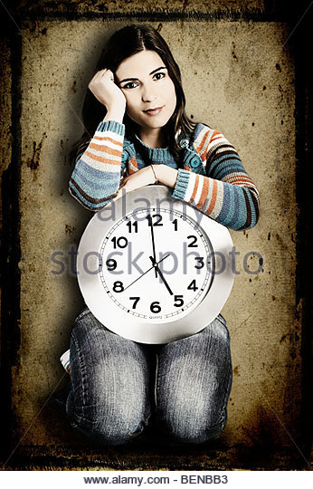 Beautiful women over knees holding a big clock with a grunge background on the back (manipulated in PS) - Stock Image