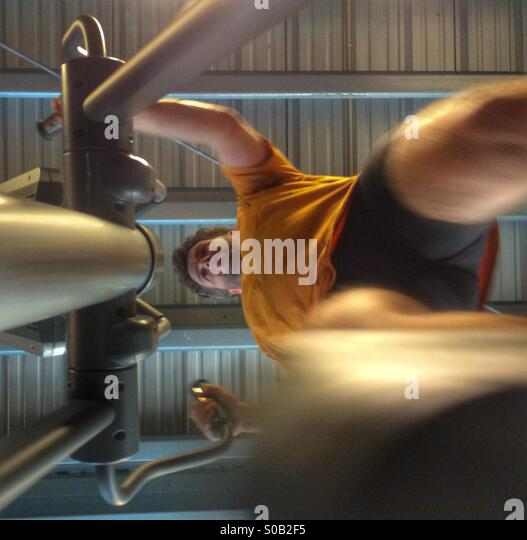Middle aged, caucasian man training on a crosstrainer/elliptical machine in a training studio. - Stock Image