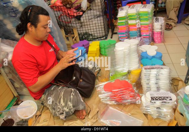 Bangkok Thailand Chatuchak Jatujak Weekend Market J.J. marketplace flea shopping Asian man smartphone manager owner - Stock Image