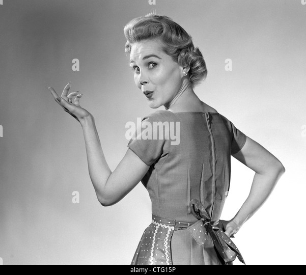 1950s HOUSEWIFE WOMAN WEARING APRON WHISTLING IN SURPRISE POINTING HAND STUDIO - Stock Image