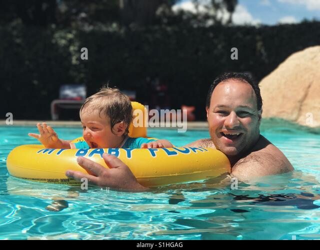 Father and baby boy having fun in swimming pool - Stock Image