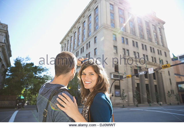Portrait of smiling woman with man photographing building - Stock Image