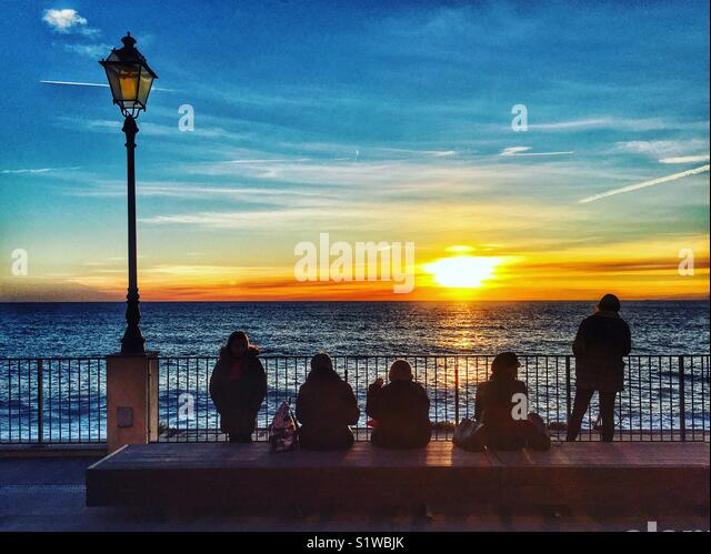 Five silhouetted figures watch the sun set over the Mediterranean, Camogli, Italy - Stock Image