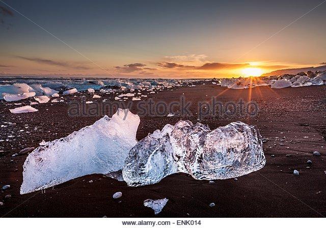 Broken ice from washed up icebergs on Jokulsarlon black beach at sunset, Jokulsarlon, southeast Iceland, Iceland, - Stock-Bilder