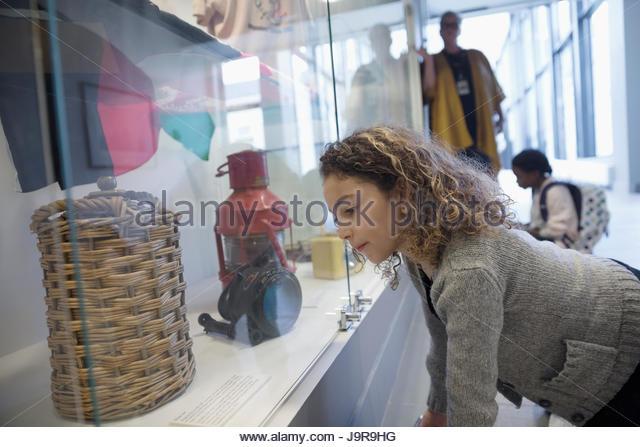 Curious girl student looking at exhibit artifacts in war museum - Stock-Bilder