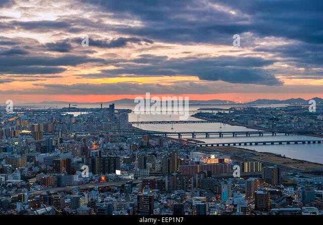 The sun sets over Osaka, Japan. - Stock Image