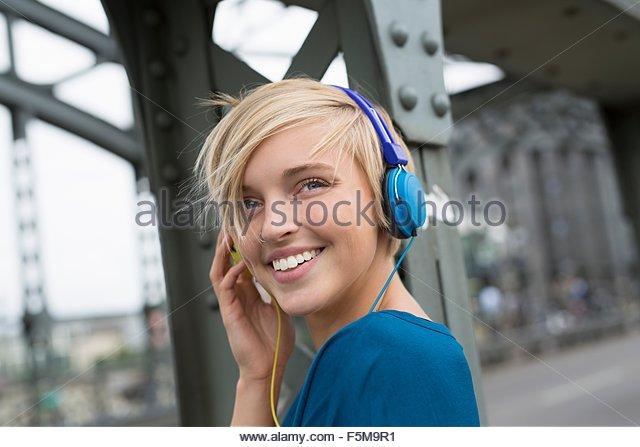 Happy young woman wearing headphones on bridge looking over her shoulder - Stock-Bilder