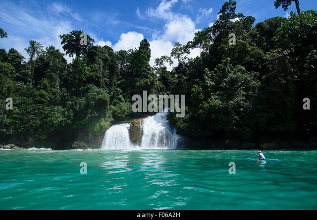 A kayaker paddles past a waterfall plummeting into the ocean, Mommon, Banda Sea, West Papua province, Indonesia, - Stock Image