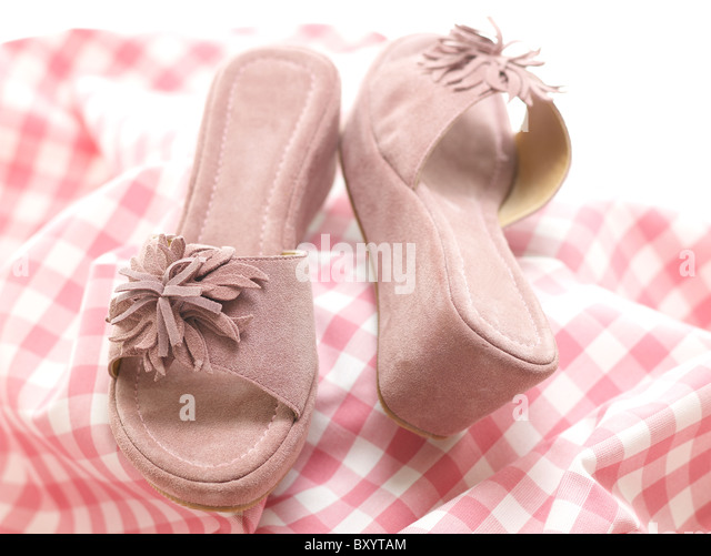 pair of womens shoes/sandals wedge on a gingham background - Stock Image