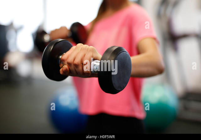 Woman at sport fitness gym weight training for beauty body. Fitness girls with dumbbells. - Stock Image