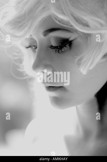 A woman wearing a blonde wig with a Marilyn Monroe look - Stock Image