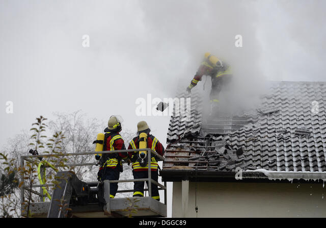 Firefighters wearing breathing equipment while extinguishing a roof fire, removing the roof tiles to access the - Stock Image