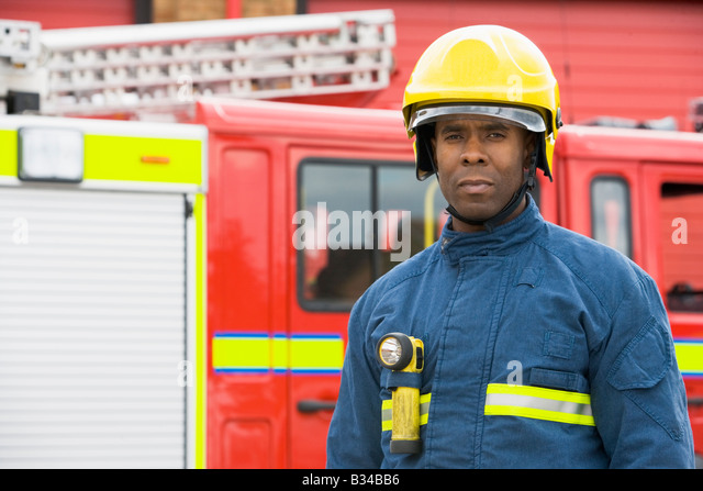 Fireman standing by fire engine wearing helmet - Stock Image