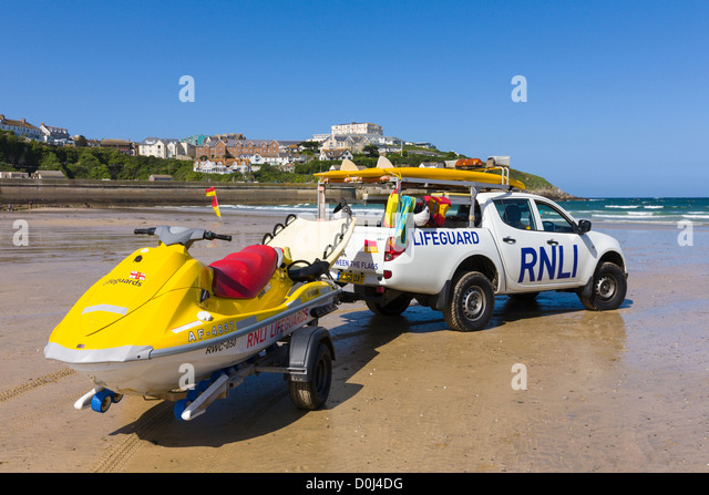 RNLI lifeguard vehicle and surfboard keeping watch over Great Western Beach, Newquay, Cornwall - Stock Image