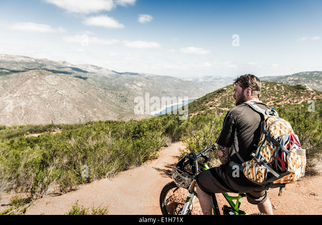 Downhill mountain biker looking at view - Stock-Bilder