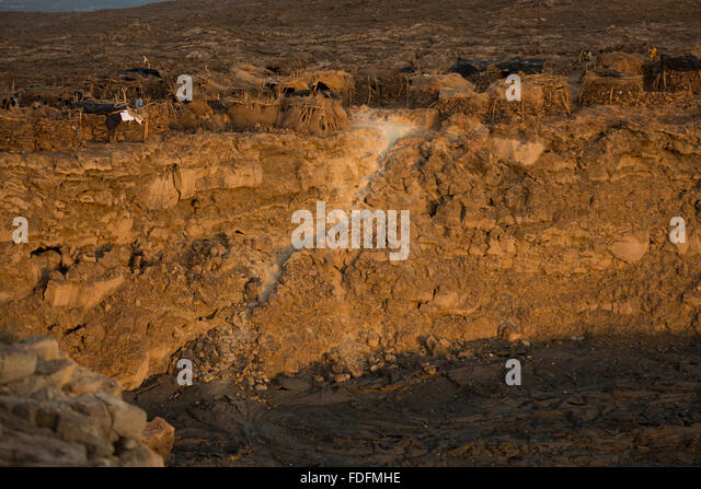 The rising sun lights up the cliffs under the encampment on the crater edge of Erta Ale volcano - Stock Image