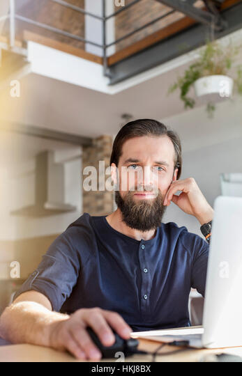 Portrait confident male design professional working at laptop in office - Stock-Bilder