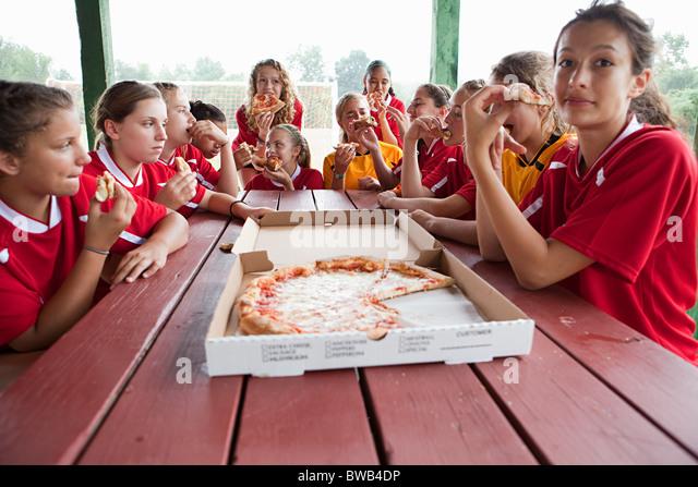Female soccer team having pizza - Stock Image