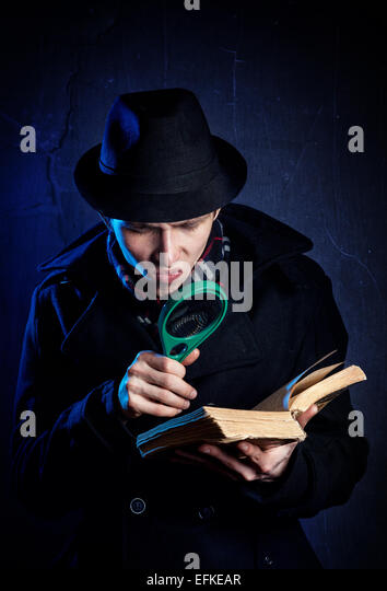 Man in black hat with magnifier glass reading the old book at dark background - Stock Image