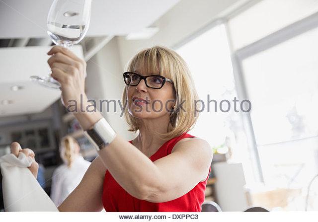 Bistro owner checking wine glasses - Stock Image