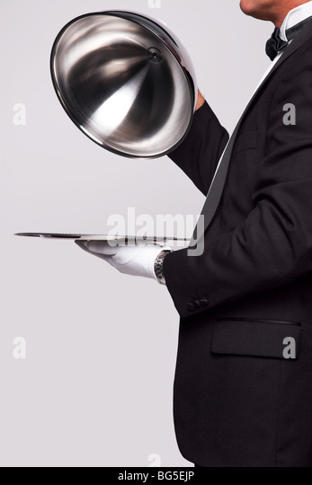 Butler lifting the cloche from a silver serving tray, insert your own object onto the tray. - Stock Image