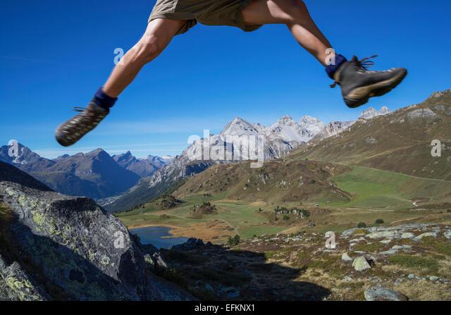Legs of male hiker jumping over rocks, Lai da Fons, Canton Graubunden, Switzerland - Stock Image