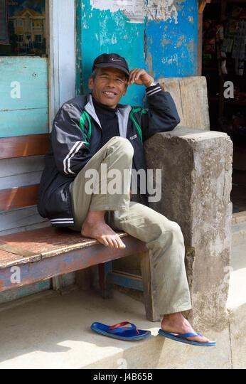Nepalese man sitting on a bench, Bahundanda, Annapurna region - Stock-Bilder