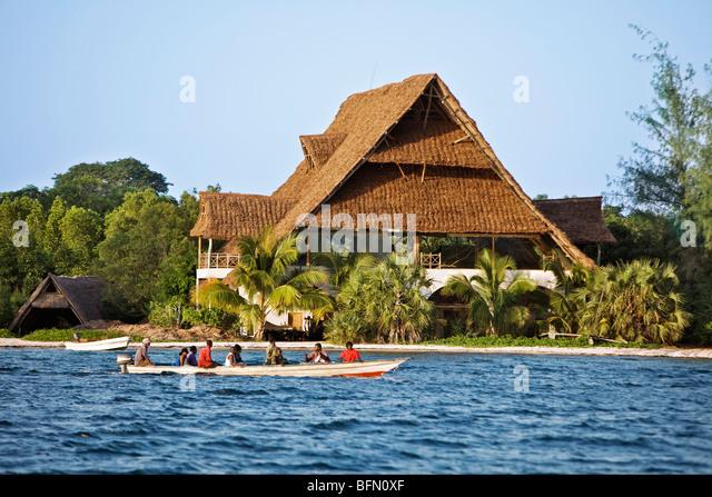 Kenya, Mombasa. Passengers being ferried to Funzi Island, off Kenyas south coast, pass an elegant house made of - Stock Image