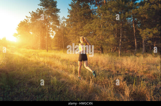 Young sporty girl running on a field near the trees at sunset in summer. Athlete running on the off road in the - Stock-Bilder