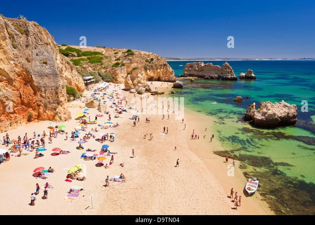 Travel Holidaymakers sunbathing on Praia da Dona Ana sandy beach near the resort of Lagos Algarve Portugal EU Europe - Stock-Bilder