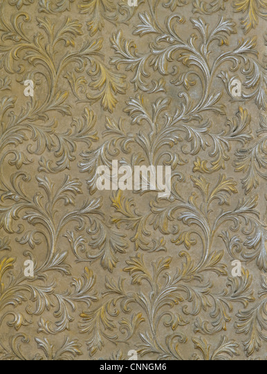 fragment of the cement wall with the silver and gold leaves - Stock-Bilder