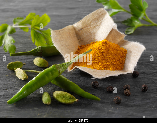 Fresh green birdseye chillies with ground turmeric & coriander leaves Indian spices - Stock Image