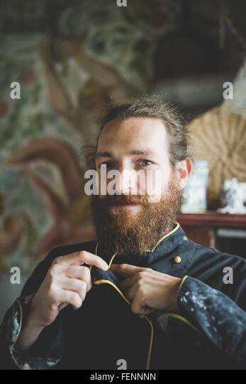 Portrait of bearded mid adult man buttoning up clay covered jacket, looking at camera smiling - Stock Image