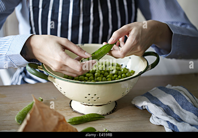 Man removing peas from pods - Stock Image