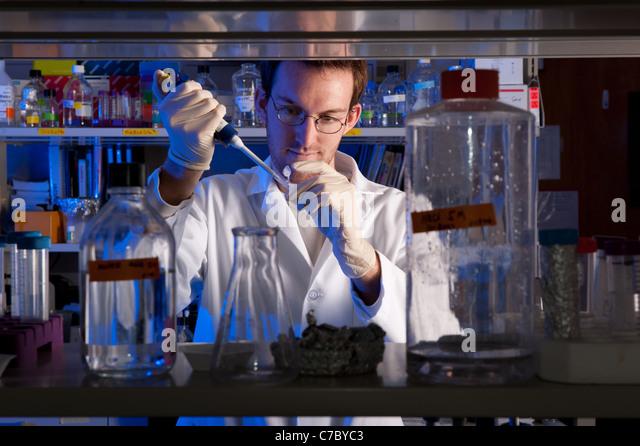 Scientist conducting experiment in lab - Stock-Bilder