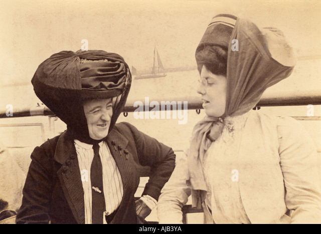 Unusual photograph of two relaxed Edwardian ladies on deck of a steamer wearing hats secured with scarves - Stock Image
