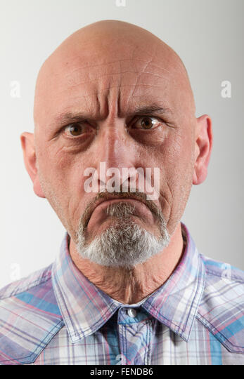 Close-Up Portrait Of Angry Man Against Gray Background - Stock Image