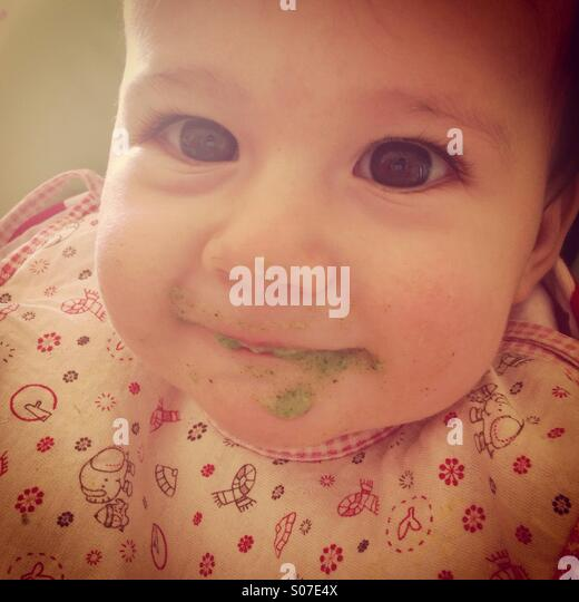 Messy baby girl eating lunch and smiling - Stock Image