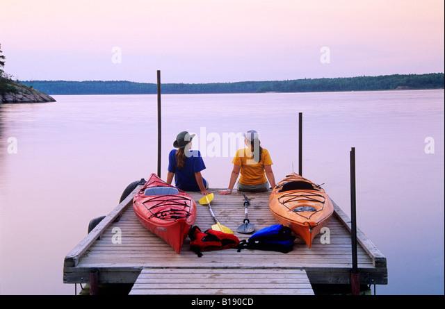 Kayakers an Nutimik Lake campground boat dock, Whiteshell Provincial Park, Manitoba, Canada. - Stock-Bilder