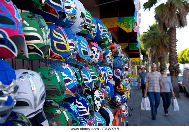 Shoppers pass by a stand selling Mexican wrestling masks, which serve as colorful reminders of the Latin American - Stock Image