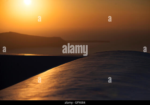 A warm sunset on the beautiful and romantic Greek Island of Santorini. Taken from one of the many restaurants and - Stock Image