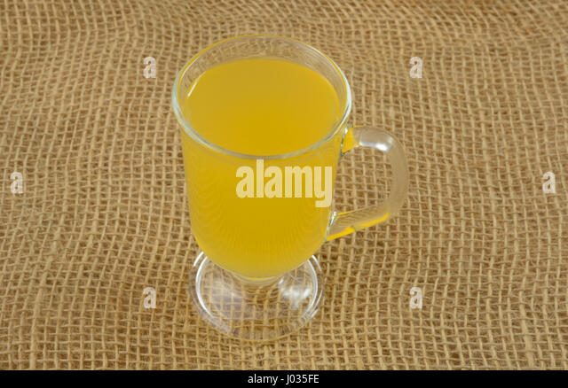Yellow passionfruit fruit juice drink in glass on burlap - Stock Image