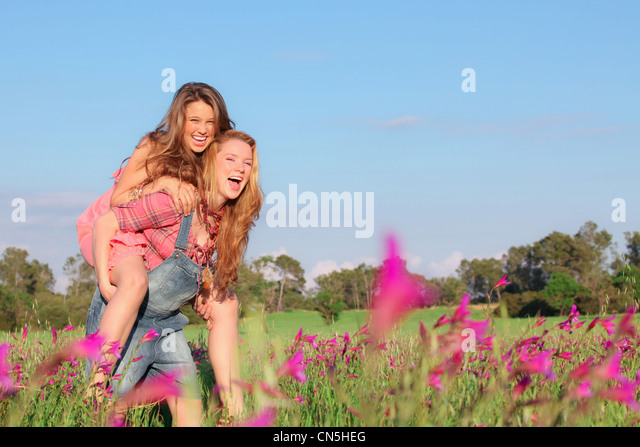 happy smiling spring or summer piggy back teens or teenager kids - Stock Image
