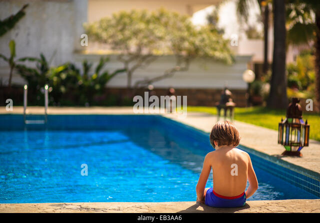 Boy sitting on edge of swimming pool - Stock Image