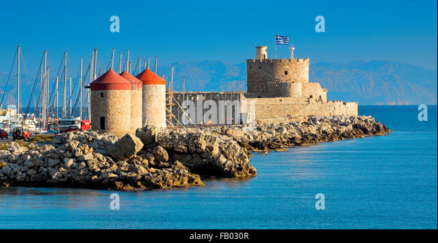 The Castle and old windmills at the enterance to Mandraki harbour in Rhodes, Greece - Stock-Bilder