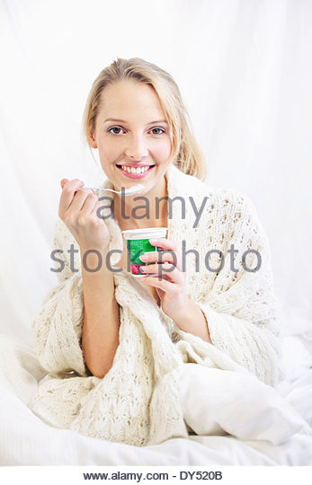 Young woman eating yoghurt, smiling - Stock Image