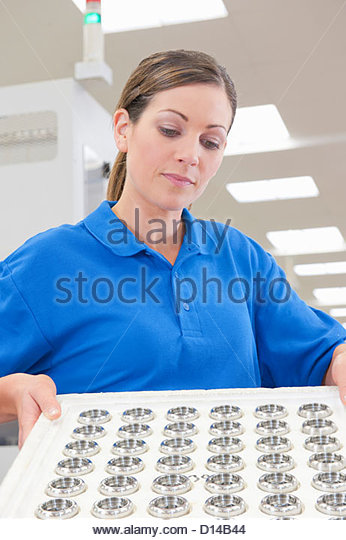Engineer examining finished machine parts in manufacturing plant - Stock Image