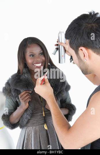 Hair stylist makes adjustments to model in fake fur jacket - Stock Image