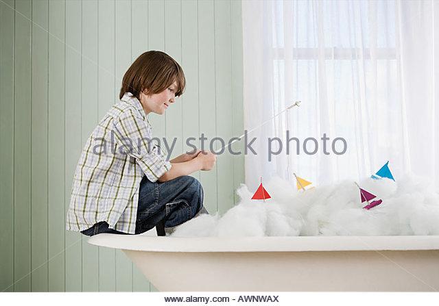 A boy fishing in a bathtub - Stock Image