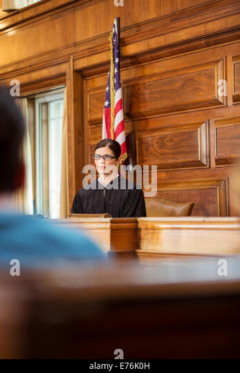 Judge sitting at judges bench in court - Stock Image